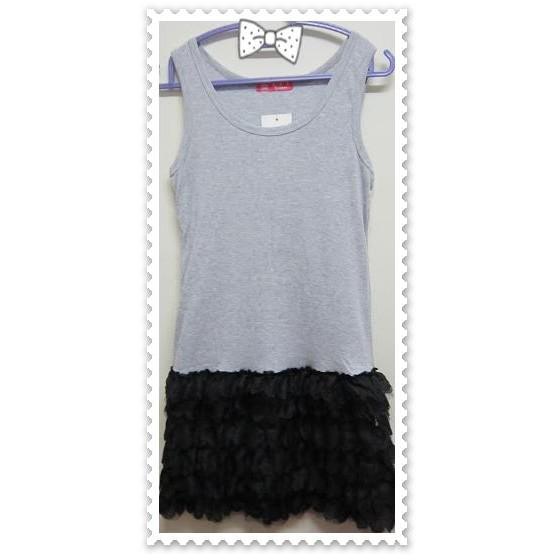 Grey Sleeveless Dress Features A Round Neckline And A Black Tiered Hem.