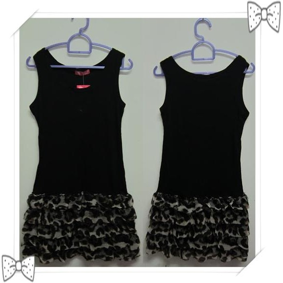 Black Sleeveless Dress Features A Round Neckline And A Black Tiered Hem.